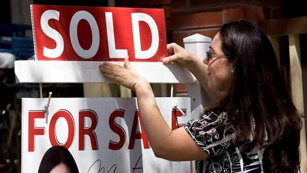A real estate agent puts up a sold sign in front of a house in Toronto. Economists say trying to determine housing market price trends from average price data is 'like looking in a funhouse mirror.'