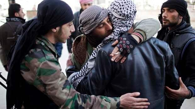Free Syrian Army fighters console a comrade after an ambulance carried an injured friend to a hospital during fierce fighting against government troops in Idlib on Saturday.