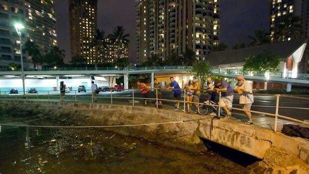 Visitors and Oahu residents in Honolu watch the water level in Ala Wai Harbour while waiting for the arrival of a tsunami Saturday, Oct. 27, 2012, in Honolulu.