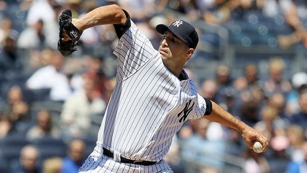 New York Yankees pitcher Andy Pettitte throws a first inning pitch Sunday against the Seattle Mariners in his first major league appearance since retiring after the 2010 season.