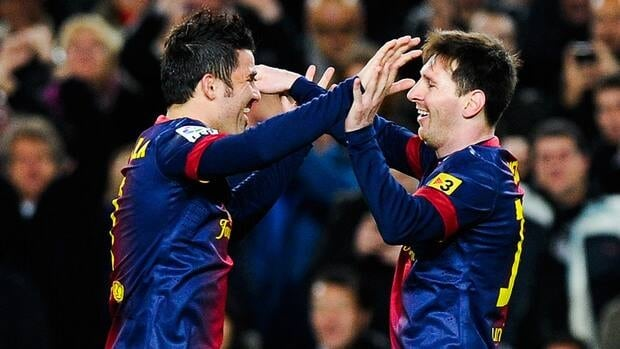 Lionel Messi of Barcelona, right, celebrates with teammate David Villa after scoring against Rayo Vallecano at Camp Nou on March 17, 2013 in Barcelona, Spain.