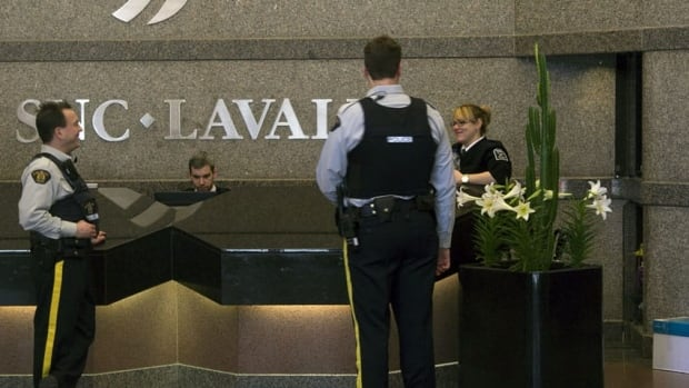 RCMP officers stand guard in the headquarters of SNC-Lavalin in Montreal last April while their colleagues execute search warrants. CBC News has learned that the Mounties are helping a Swiss investigation into $139 million in mysterious payments by the company.