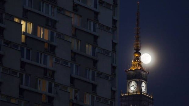 The moon is seen above the Palace of Culture and Science in the centre of Warsaw, on April 24, 2013.