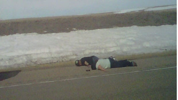 Two suspects prone on the side of the highway moments before an RCMP shooting.