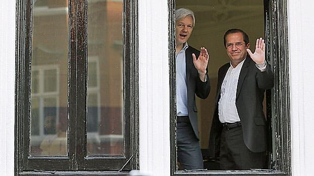 WikiLeaks founder Julian Assange waves from a window of the Ecuadorian embassy in London on Sunday, alongside Ecuador's Foreign Affairs Minister Ricardo Patino. On June 19, he will have been there one year.