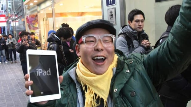 A Korean customer reacts after getting his hands on a new iPad in Seoul. Worldwide, Apple has less of the global tablet share than it used to.