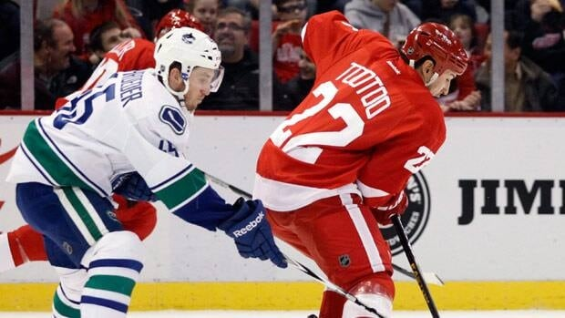 Vancouver Canucks center Jordan Schroeder (45) tries to steal the puck from Detroit Red Wings right wing Jordin Tootoo (22) during the first period of an NHL hockey game Sunday, Feb. 24, 2013, in Detroit. (AP Photo/Duane Burleson)