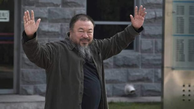 Chinese activist artist Ai Weiwei waves to the journalists as he arrives at a Beijing court in 2012. His latest project is a heavy metal album.