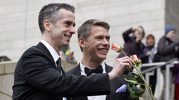 Dan Savage, left, and his husband Terry Miller are handed flowers after their wedding at Seattle City Hall last December after the state's governor signed a voter-approved law legalizing gay marriage.
