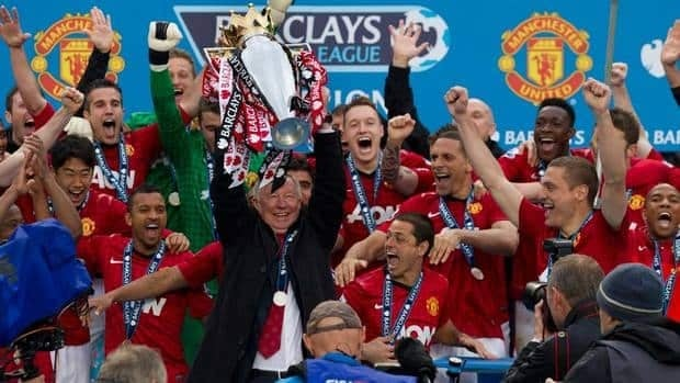 Manchester United's manager Sir Alex Ferguson lifts the premier league trophy after his last home game in charge of the club on Sunday.