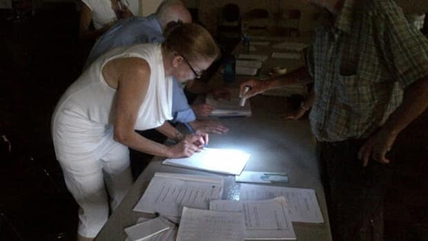 Voters used flashlights to see after electricity was cut at their polling station.