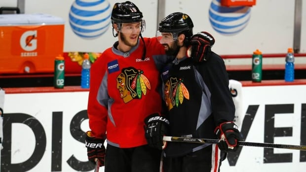 Blackhawks centre Jonathan Toews, left, chats with teammate Nick Leddy during practice Friday in Chicago, as they prepare for Game 5 of the Stanley Cup final against the Boston Bruins.