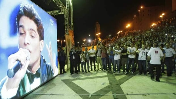 Palestinians watch the performance of Palestinian singer Mohammed Assaf, a contestant in the regional TV singing contest Arab Idol, on a large screen in the West Bank city of Nablus.
