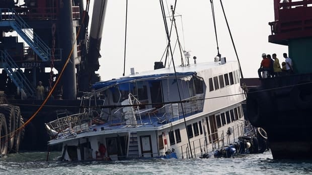 A boat is lifted by cranes Tuesday after a collision on Monday night off the southwestern coast of Hong Kong. The boat, which was packed with revelers on a long holiday weekend, collided with a ferry and sank, killing at least 38 people and injuring dozens.