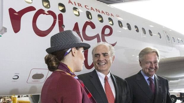 Air Canada president and CEO Calin Rovinescu, centre, chats to Air Canada Leisure Groups president and CEO Michael Friisdahl and flight attendant Stephane Dolanhangar during the unveiling of one of the airplanes that will be used by the airline's new discount leisure carrier, Rouge, at Toronto's Pearson Airport on Tuesday.
