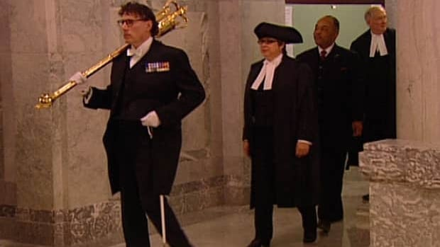 Speaker Mary Anne Jablonski is led into the house where she presided over question period as the first woman ever to do so at the Alberta Legislature.