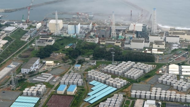 An aerial view shows Tokyo Electric Power Co.'s tsunami-crippled Fukushima Daiichi nuclear power plant and its contaminated water storage tanks, bottom, in Fukushima. Japan's nuclear watchdog is concerned that more storage tanks at the wrecked Fukushima nuclear plant will spring leaks, following the discovery that highly contaminated water is leaking from one of the hastily built containers.