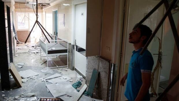 A man inspects damage from an airstrike last August at the Dar al-Shifa hospital.
