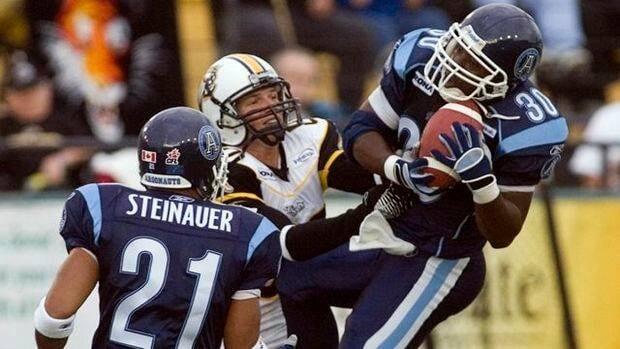Toronto Argonauts Orlondo Steinauer (21) looks on as teammate Kenny Wheaton pulls in an interception away from Hamilton Tiger-Cats Brock Ralph a 2006 CFL game in Hamilton.