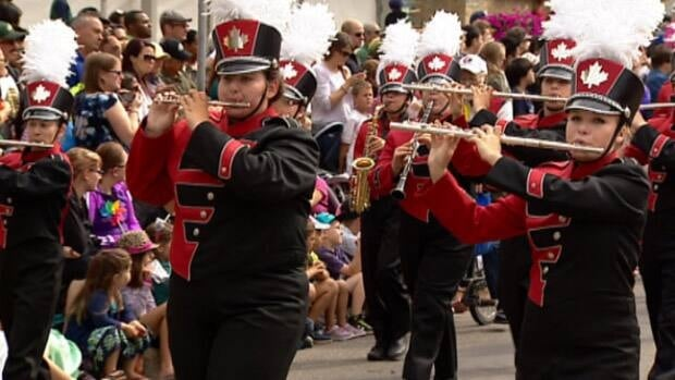 A marching band plays as people pack downtown streets Friday morning for the K-Days parade, kicking off the newly-renamed summer fair. (Scott Neufeld/CBC)
