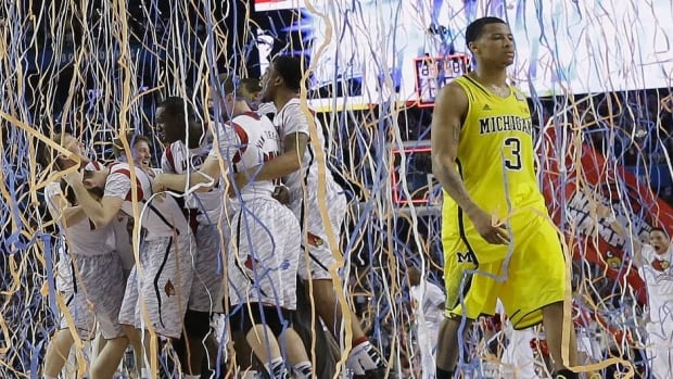 Michigan guard Trey Burke (3) walks off the court as Louisville celebrates their win after the second half of the NCAA Final Four tournament college basketball championship game Monday, April 8, 2013, in Atlanta. Louisville won 82-76. (AP Photo/Charlie Neibergall)