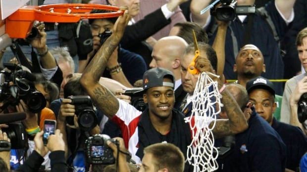 Injured Louisville Cardinals guard Kevin Ware displays the net he cut down after his team defeated the Michigan Wolverines to win the NCAA men's championship in Atlanta, Georgia on Tuesday.