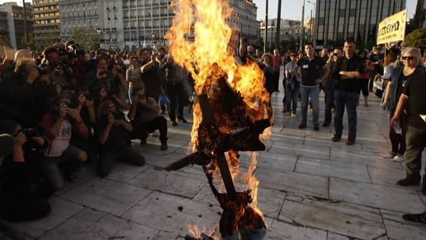 A few hundred public servants protested peacefully Sunday outside the Greek parliament as legislators voted on a new austerity bill that will cut civil service jobs.
