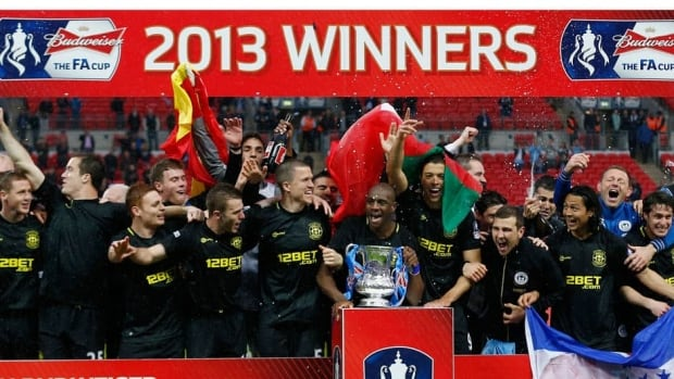 Wigan Athletic's players celebrate with the FA Cup after beating Manchester City 1-0 in Saturday's final match at Wembley Stadium.