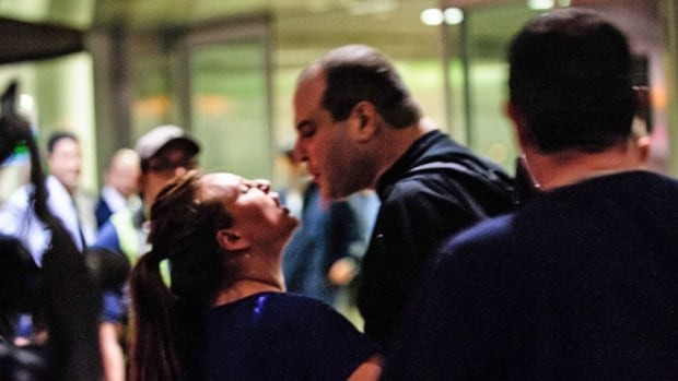 A man spits into the face of an Air Canada baggage handler during a wildcat walkout at Toronto's Pearson International Airport early Friday. The job action began Thursday evening and left hundreds of passengers in limbo after they had to disembark from several flights already on the tarmac.