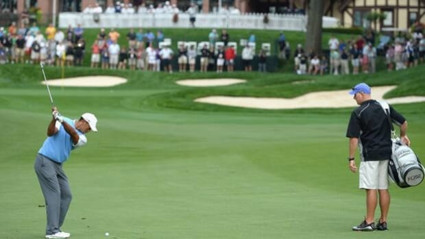 Tiger Woods hits an approach shot in Tuesday's practice round at Oak Hill in Rochester, N.Y.