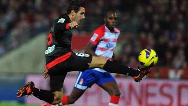 Atletico Madrid's midfielder Koke moves dwon the field as Granda defender Allan Nyom keeps pace.