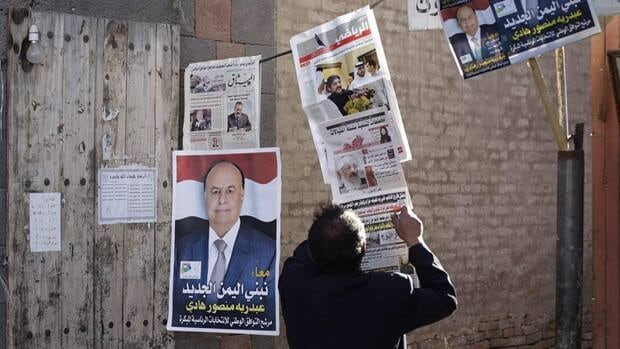 A Yemeni newspaper vendor waits for customers in his stall displaying a campaign poster of Vice-President Abed Rabbo Mansour Hadi in the old the city of Sanaa, Yemen, Feb. 16.