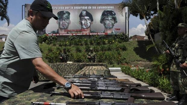 A soldiers arranges weapons and ammunition seized from rebels of the Revolutionary Armed Forces of Colombia, or FARC. Canada has eased its ban on the export of assault-style weapons to Colombia.