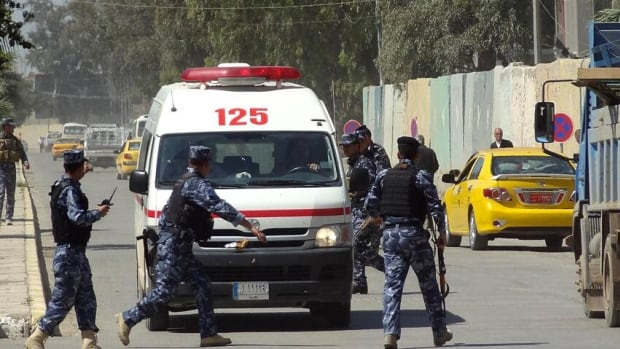 Iraqi soldiers surround an ambulance as it arrives at a hospital following clashes between security forces and anti-government protesters, allegedly infiltrated by militants, on April 23, in the northern city of Kirkuk.