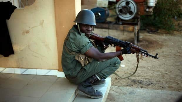 A Malian soldier takes cover behind a wall during exchanges of fire with jihadists in Gao on Sunday.