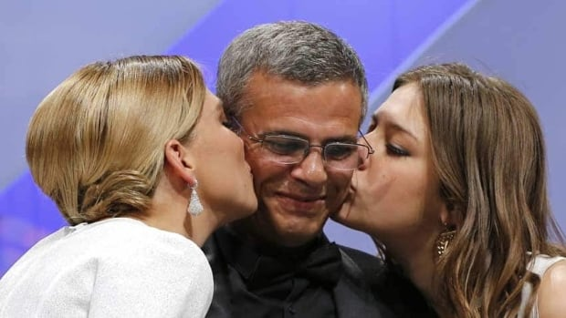 Actresses Lea Seydoux, left, and Adele Exarchopoulos kiss director Abdellatif Kechiche on stage after receiving the Palme d'Or award for the film La Vie D'Adele at the Cannes Film Festival.