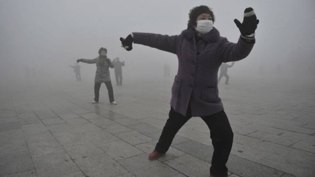 A woman wears a mask as she does her morning exercise outdoors in Fuyang, China, as the country's environmental watchdog ordered greater efforts to issue early warnings for air quality.