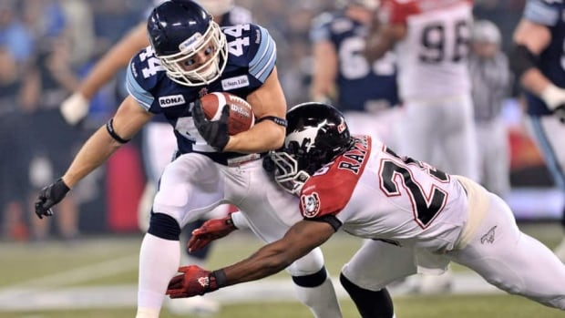 Toronto Argonauts running back Chad Kackert runs the ball against Calgary Stampeders defensive back Keon Raymond during Grey Cup action.