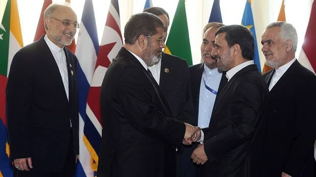 Egyptian President Mohammed Morsi, left, shakes hands with Iranian President Mahmoud Ahmadinejad at the opening session of the Nonaligned Movement summit, in Tehran, Iran, on Thursday.