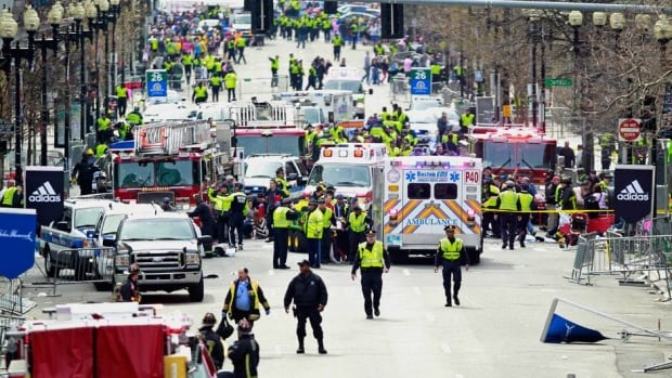 Police clear the area at the finish line of the 2013 Boston Marathon as medical workers help injured people following explosions in Boston on Monday.