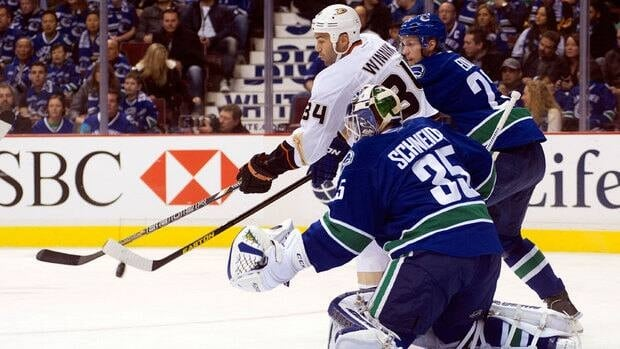 Daniel Winnik (34) of the Anaheim Ducks deflects the puck past goalie Cory Schneider (35) of the Vancouver Canucks while being checked by Alexander Edler (23) Saturday at the Rogers Arena.