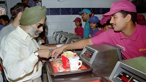 A customer buys food at McDonald's first location in India in 1996. The chain will open vegetarian-only locations next year.