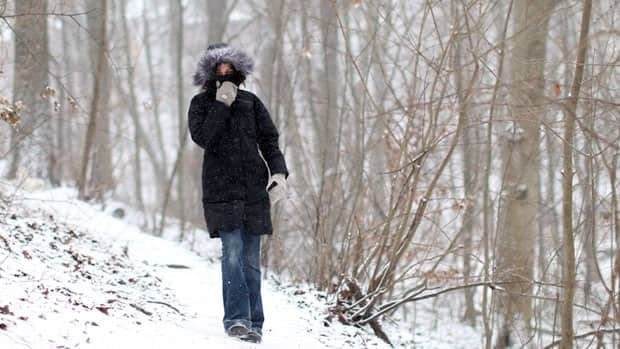 A woman walks through a ravine in Toronto's east end on Tuesday. The city has issued an extreme weather warning.