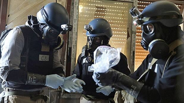 A UN chemical weapons expert, wearing a gas mask, holds a plastic bag containing samples from one of the sites of an alleged chemical weapons attack in the Ain Tarma neighbourhood of Damascus August 29.