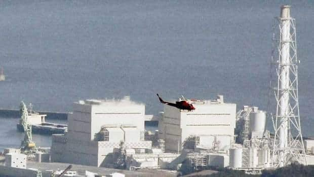 A helicopter flies over the Fukushima Dai-ichi nuclear plant in 2011. A report suggests the Japan government was less than candid with its citizens and allies about how much worse the disaster could have become.