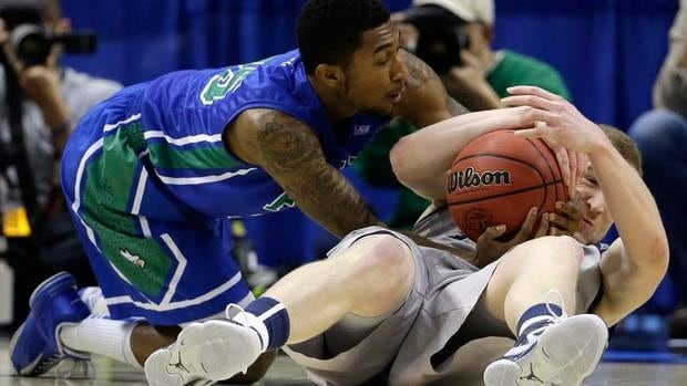 Florida Gulf Coast's Dajuan Graf, left, struggles for a loose ball with Georgetown's Nate Lubick during the first half their game in Philadelphia on Friday. FGCU became the 5th No. 15 seed in history to beat a No. 2.