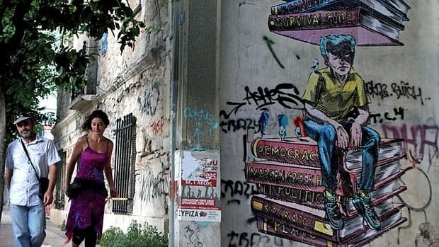 The weather is fine but there are few tourists as a couple walks by the graffiti and riot-damaged buildings in central Athens in June 2012.