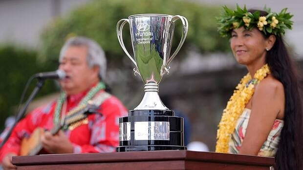 Hyundai Tournament of Champions Cup is displayed alongside musician George Kahumoku Jr. and traditional hawaiian dancer, Wainani Kealoha before the first round at the Plantation Course on Friday in Kapalua, Hawaii.