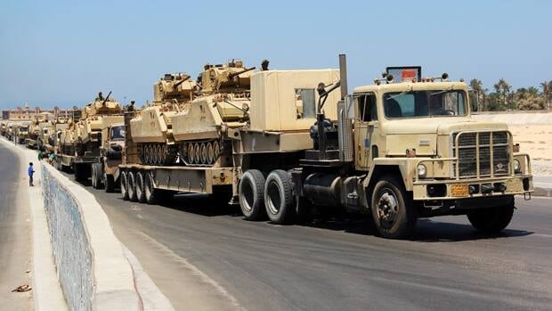 Army trucks carry Egyptian military tanks in El Arish, Egypt's northern Sinai Peninsula on Thursday, Aug. 9, 2012.