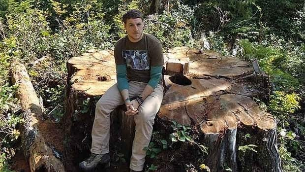 Torrance Coste sits on the stump of what is said to have been a 800-year-old red cedar that was cut down near the entrance of Carmanah-Walbran Provincial Park on Vancouver Island Saturday.